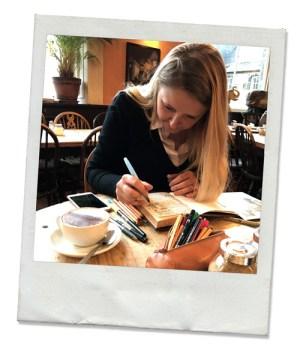 Lumi Poullaouec en train de dessiner sur son carnet paper blank à Elephant House de Edimbourg. En premier plan, sa trousse débordant de crayons et une tasse de café latte.