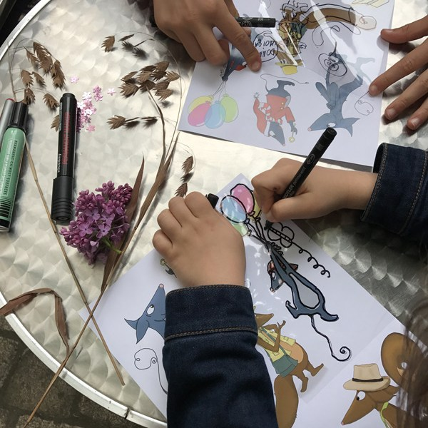 Enfant décalquant Gustaf la souris sur une feuille transparente