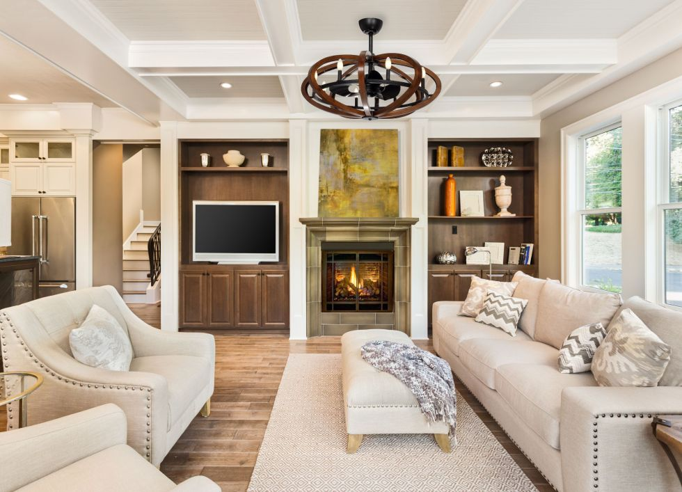 Beautiful living room with hardwood floors, coffered ceiling, and fire in fireplace in new luxury home