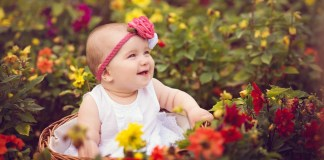 baby in a field of flowers