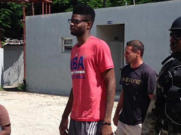 "A little Haitian onlooker walks beside Nerlens Noel as he prepares to enter Gymnasium Vincent with manager Chris Driscoll and Port-au-Prince police officer Ricot ""Mutombo"" St. Louis. (Keith Pompey/Staff) - Click Picture for Source"