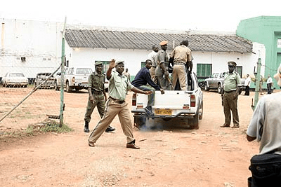 A prison guard blocking photographers from shooting pictures of Regina Chiluba at Chimbokaila