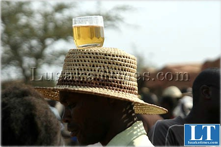 An unidentified man balacing a beer glass on his head