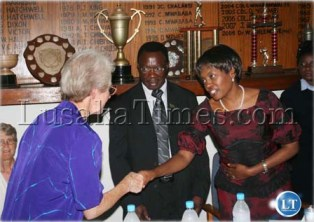 First Lady Thandiwe Banda shakes hands with Umoyo Day Center for Orphans Manager, Sister Edna O'Connor as Chainama Golf Club Captain, Colonel Collins Mwanamwali (center) looks on during the Our Lady's Hospice fundraising golf tournament prize presentation in Lusaka.