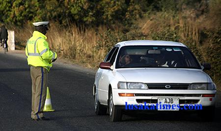 A traffic policeman attending to a motorist at a roadblock