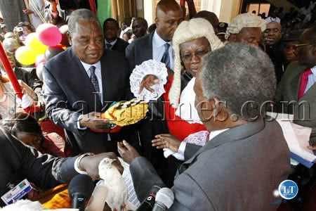 President Michael Sata receives instruments of power from outgoing President Rupiah Banda as Chief Justice Ernest Sakala looks on at the inauguration ceremony at the Supreme Court in Lusaka