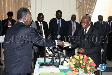 President Michael Sata receives an affidavit from newly appointed Minister of Justice Sebastian Zulu at the swearing-in ceremony at State House