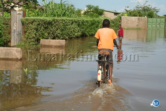 FILE: A boy cycling through a flooded street in Chowa Township following heavy rains at the weekend
