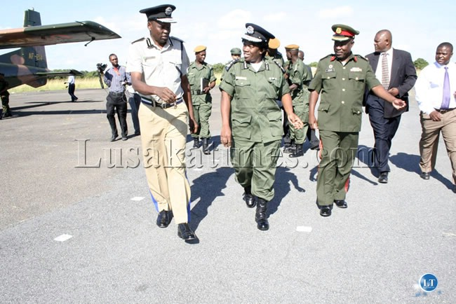 Western Province Commissioner of police Fanwell Siamundenge (l) and Colonel Chewe (r) welcomes Inspector General of Police Stella Libongani at Mongu airport.