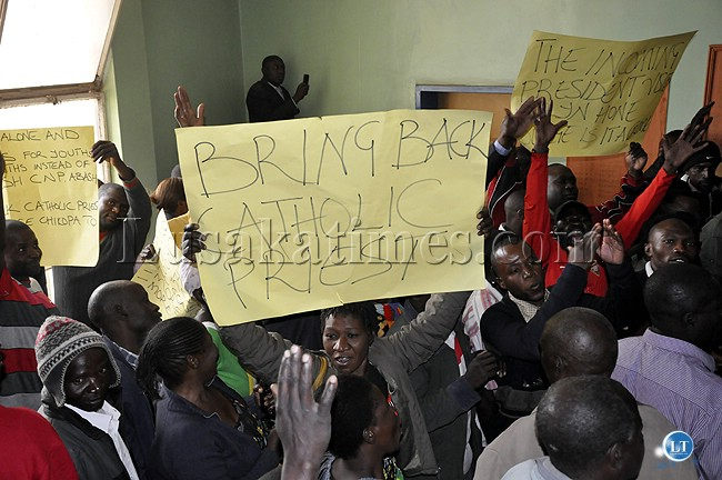 A UPND cadre shows a poster to demand the return of Rwanda priest Banyangandora who was deported by the government recently