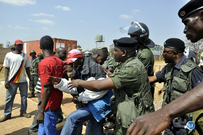 File Picture: Police officers push a PF youth who wanted to start a fight with UPND cadres