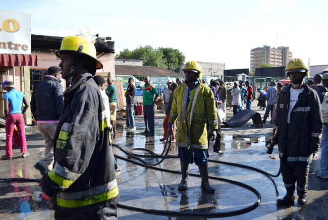 FIREFIGHTERS from the Fire Brigade preparing to leave after quenching the fire that swept through several shops at ZIMCO yard along Freedom Way in Lusaka