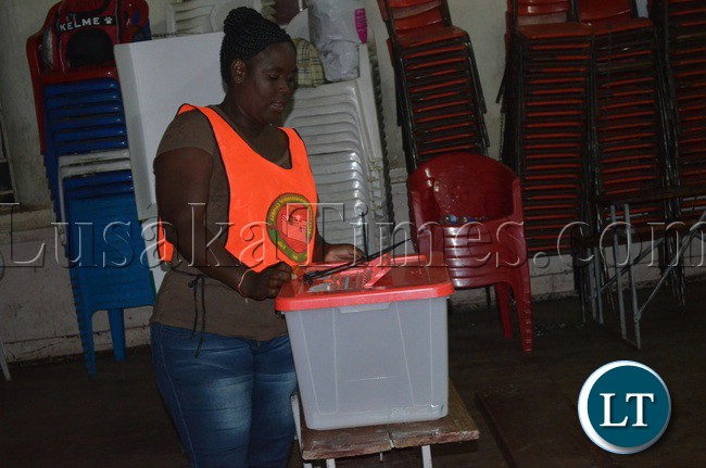 Electoral officers checking the ballot boxes