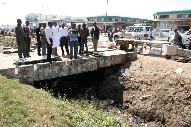 Local Government Deputy Minister John Kufuna (c) pointing at the blocked drainage on Lumumba Road near Lumumba Bus Station in Lusaka during his Inspection Tour for Performance Based Contractor Projects,