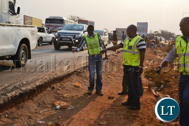 Road Traffic and Safety Agency director Zindaba Soko (c) and Principal Engineer Mubanga Mulenga(l) pointing at the run-down edge of the Kitwe-Chingola Road cited as a safety hazard