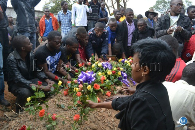 COPPERBELT University Students Union (COBUSU) members make a circle round the grave of their deceased colleagues during burial