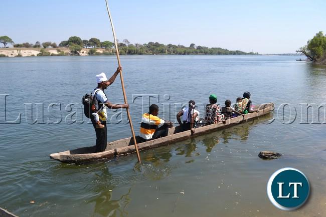 Gift Chingimbu balances a baby of one of his passengers on his back as he paddles away his canoe across the Zambezi River for the Likumbi Lyamize traditional ceremony.