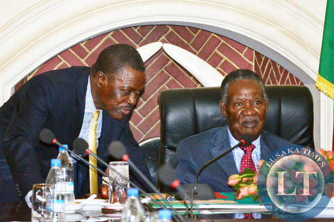 President Michael Sata listens to Justice Minister Wynter Kabimba (left) at the launch of the African Peer Review Mechanism report at State House in Lusaka