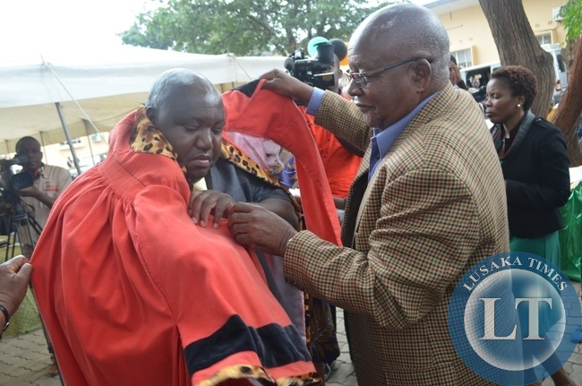 Southern Province Minister Daniel Munkombwe (right) and Livingstone Town Clerk Vivian Chikoti (middle) dresses the newly elected mayor for Livingstone Milford Maambo (left) during the installation of the mayor and deputy mayor in the tourist capital