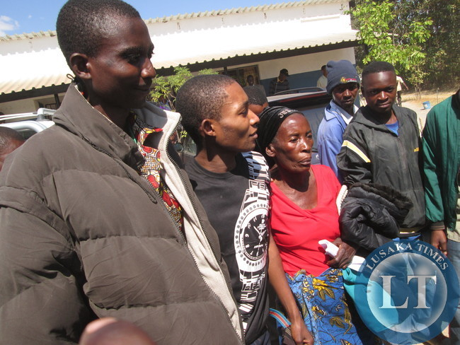 Philip Mubiana  in the middle in a black t-shirt  with her grandmother outside court after  his acquittal