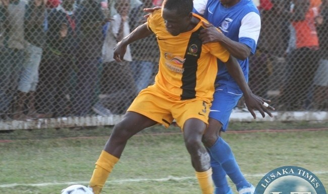 Power Dynamos Captain Emmanuel Chimpinde (left) is dragged back by Kabwe Warriors player Michael Katongo during week 16 FAZ- MTN Premier league game played at Ucar Chitalu Stadium in Kabwe yesterday . Power won by 3 - 2