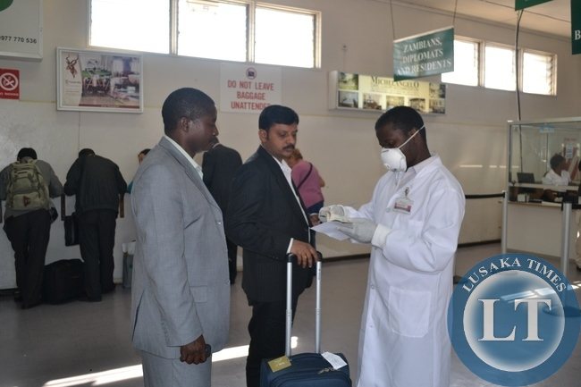 FILE: A HEALTH official going through a medical card of a passenger who had just disembarked an international flight at the Simon Mwansa Kapwepwe International Airport in Ndola . The process is part of screening for Ebola at entry points into Zambia.