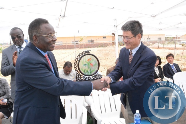 Minister of Health Joseph Kasonde shakes hands with Chinese Ambassador to Zambia Yang Yaoming shortly after receiving a double Fish ornament during the unveiling ceremony of Medical Park at multi facility Economic Zone