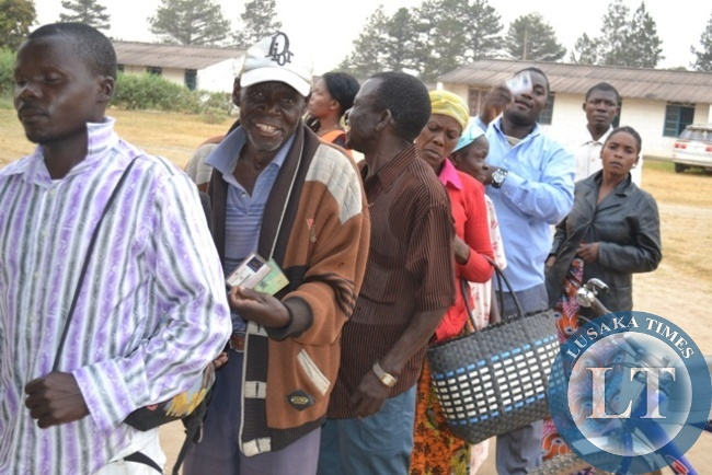 VOTERS displaying their identities while on voting queue during Solwezi Central by-elections