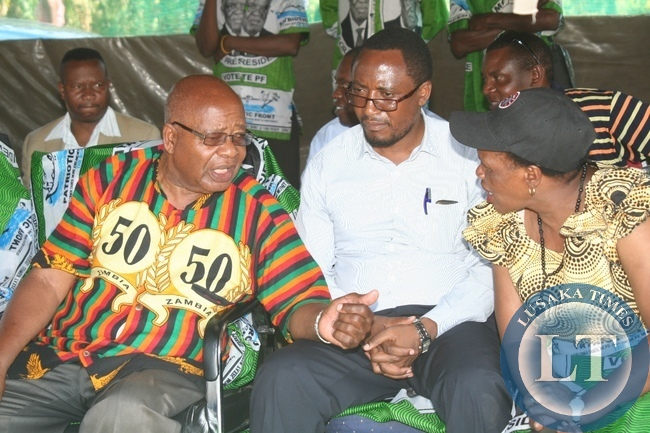 Southern Province Minister Daniel Munkombwe (l) confers with PF Deputy Secretary General Bridget Atanga (r) as Western Province Minister Richwell Siamunene (c) looks on during a PF Rally meeting at Blue Gums in Mongu District of Western Province