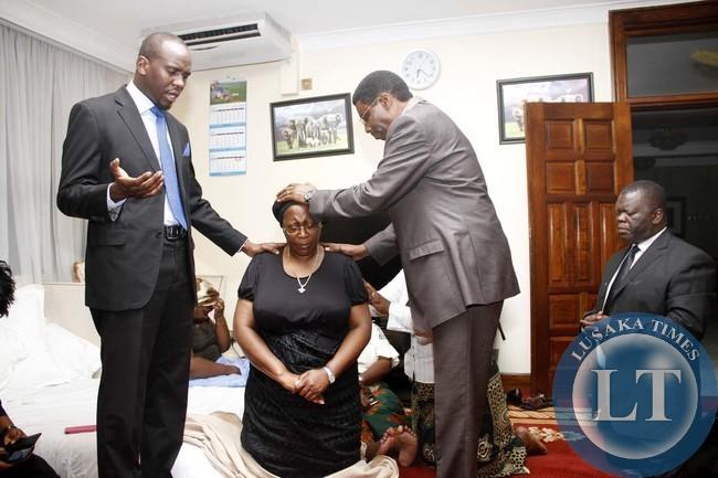 Northmead Assembly of God Bishop Joshua Banda, Pastor Haggai Mweene (l) and Dr Martin Malama (r) prays for Dr Kaseba when they visited her