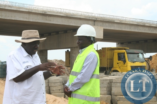 Cabinet Office Permanent Secretary for Special Duties Bert Mushala (l) confers with Road Development Agency (RDA) Western Province Regional Manager Gershom Mwagomba (r) when inspecting the construction progress of Mongu-Kalabo Road Project during the tour in Western Province to compile major developmental projects,