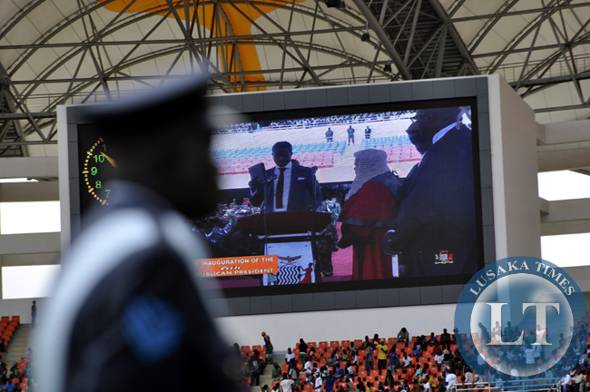 A soldier from the Zambia Air Force in front of a large screen beaming President Edgar Lungu's innauguration