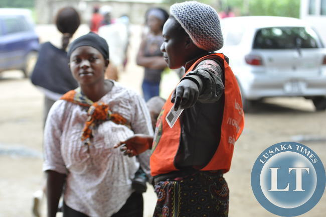 An unidentified polling officer ushers a voter into the Kanyama ward polling centre