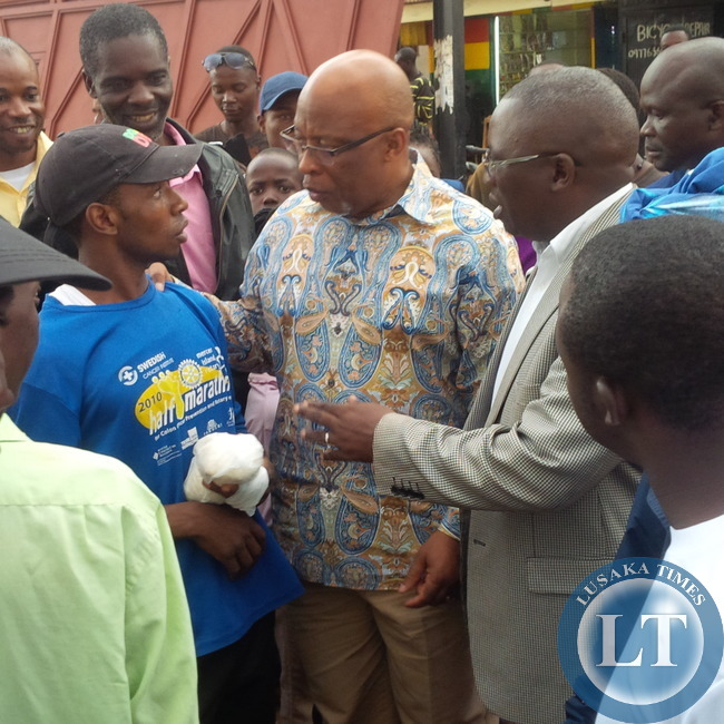 Dr Mumba chats with marketeers at Chilenje Market flanked  by supporters and MMD Acting National Secretary Mwansa Mbulakulima