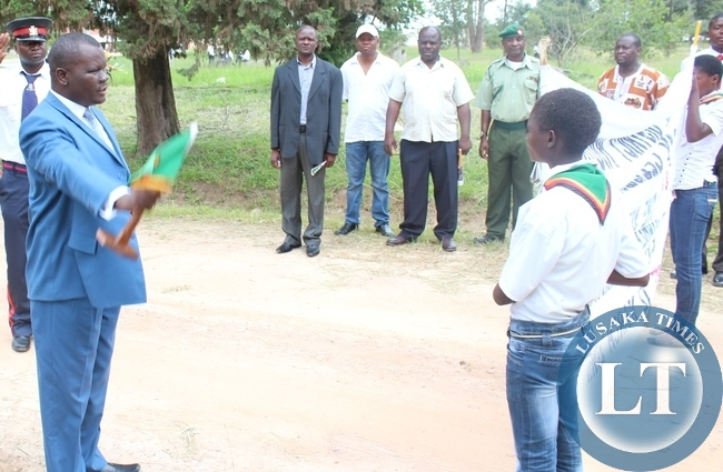 Serenje District Commissioner Charles Mwelwa flags off the Youth Match past  from his office to the national square in Serenje