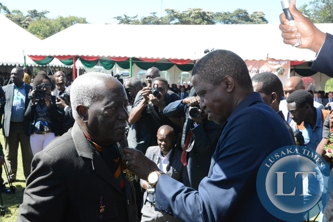 President Edgar Lungu giving a golden jubilee medal to the first Transport and Works Minister Grey Zulu during the investiture ceremony at State House
