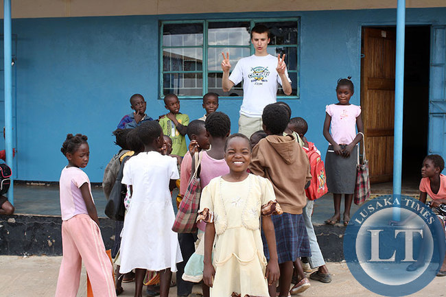 Tim Krupa plays with children orphaned by HIV and  tuberculosis in the impoverished Chazanga compound in Lusaka, Zambia.Courtesy of  Alexa Geddes