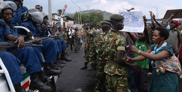 Burundian soldiers control protesters facing riot police seated in a pickup truck in Musaga, on the outskirts of Bujumbura, on April 29, 2015, during demonstrations against the President's bid for a third term. Since the protests started, the army has regularly come between the police and demonstrators to avoid further clashes and the protesters believe the soldiers are neutral. AFP PHOTO | SIMON MAINA