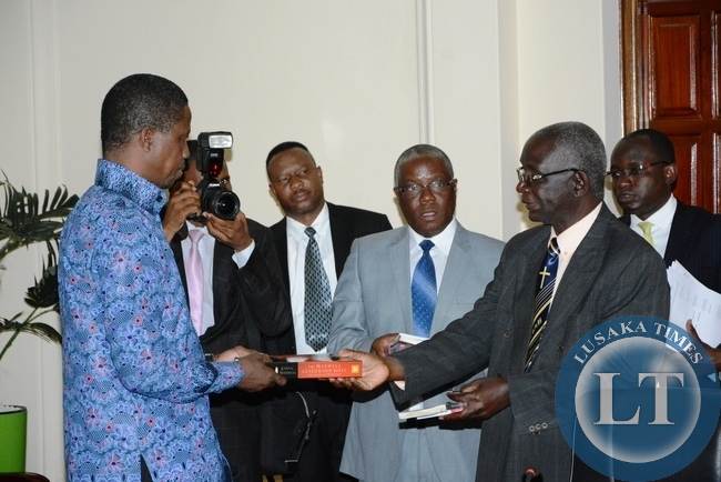 Chief Chipepo Gweembe District gives President Edgar Lungu Bible a gift shortly after President Lungu having a meeting with Southern Province Chiefs at State House whilst looking on is Southern Province minister Nathaniel Mubukwanu