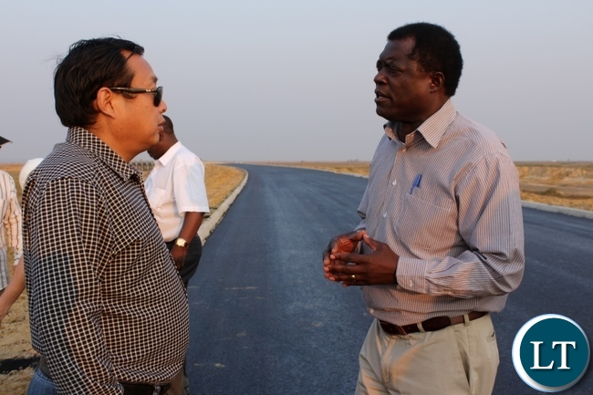 Mongu District Commissioner Susiku Kamona (r) discusses with AVIC International Zambia Limited Site Manager Chen Yiju (l) during a tour to inspect work progress on the Mongu-Kalabo Road Project