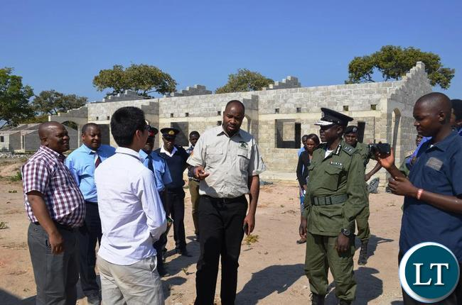 Eastern Province Minister Malozo Sichone talking to China Jiangxi Project Manager Cai Jiado Nash when he inspected a K44 million project of a boarding school under construction in Chasefu of Lundazi District