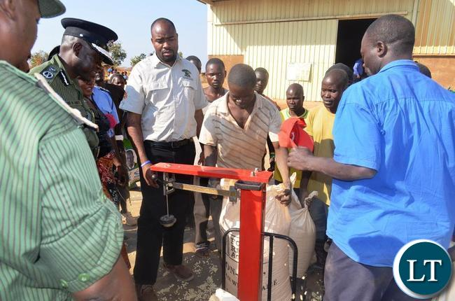Eastern Province Minister Malozo Sichone and Provincial Police Chief Eugene Sibote carefully checking the Food Reserve Agency scale at Egichickeni depot while some farmers looks on