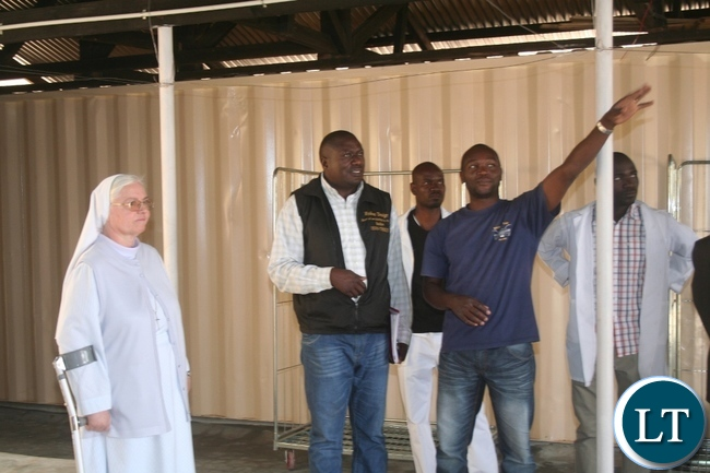North-Western province medical officer Dr Simulyamana Choonga (m) being shown newly constructed Laundry compartment at Luwi mission hospital coordinator by project Emmanuel Bwalya as  hospital founderess Dr Heide Brauckmann (l) looks on during the tour of developmental projects at the facility in Mwinilunga