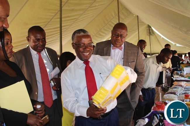 SOUTHERN Province Minister Nathaniel Mubukwanu admires a hand bag made from maheu containers. On his left is provincial Permanent Secretary Sibanze Simuchoba and Deputy permanent secretary Douglas Ngimbu (left). This was during the official opening of Southern Women Economic Empowerment Expo workshop at Woodlands lodge in Livingstone