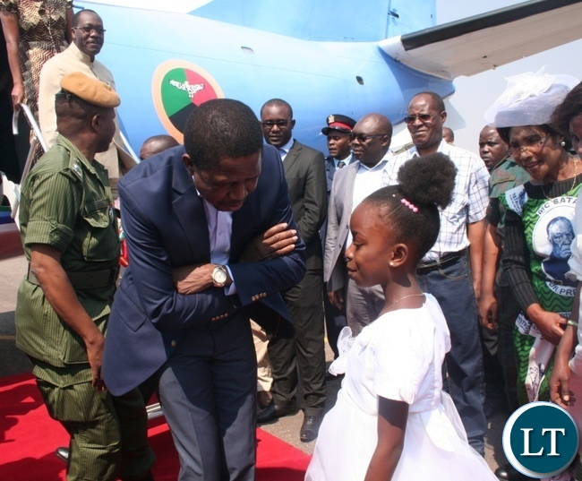 President Edgar Lungu talks to a nine year old girl Sante Mwanza upon arrival at Solwezi airport as provincial Patriotic Front (PF) women' chairlady Martha Mpila ( r) looks on in Solwez
