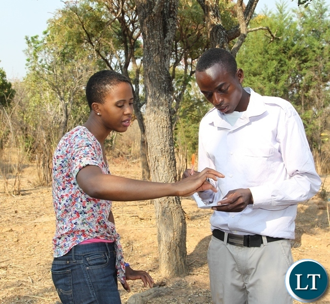 President Lungu's daughter Tasila Lungu shares notes with Leston Mwalupanga at his farm in Mwange, Mporokoso. Miss Tasila Lungu is on an invitation of touring the UNICEF and government sponsored youth programmes in Northern Province. Leston is a beneficiary of Mwange Youth Resettlement scheme funded by government and UNICEF.