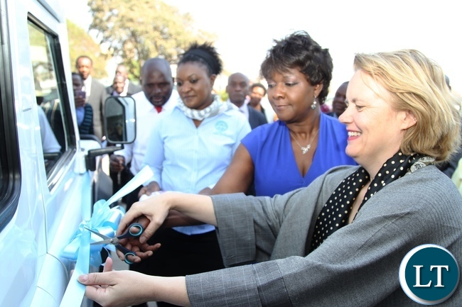 Minister of Commerce and Trade Margaret Mwanakatwe (2nr) and UNDP Country Co-odinator Janet Rogan cutting the ribbon during the hand over of the Mobile testing Laboratory to ministry of Commerce at Government Complex