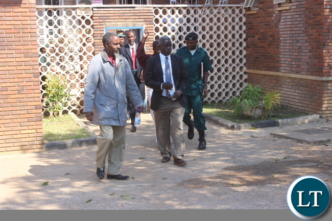 Some of Barotse accused person walking out of Kabwe High Court accompanied by a Prison officer