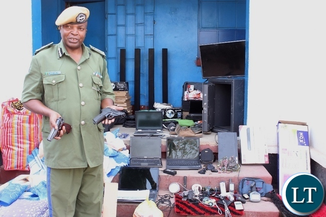 Western Province Police Commissioner Charles Lungu displays a real pistol (l) and a toy one (r) during a stolen property identification display at Mongu Central Police yesterday, recovered from suspected criminals during an operation conducted over the weekend in Limulunga and Mongu Districts. Three suspects are in custody while two are on the run.