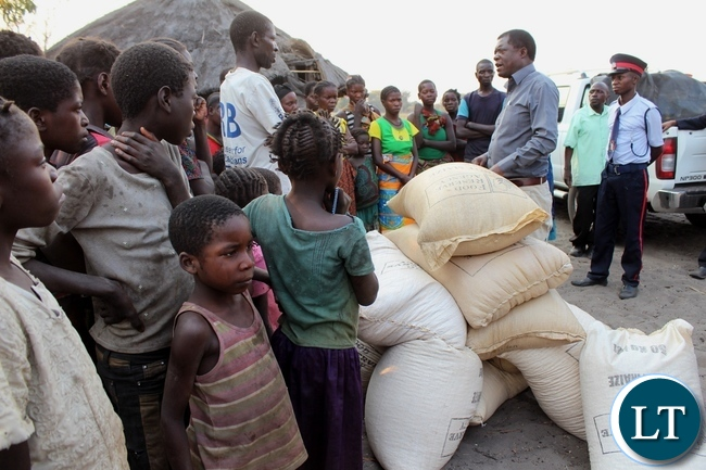 Mongu District Commissioner Susiku Kamona distributing relief maize to victims of Spastic Paralysis (Konzo) disease at Kaote Village of Lwatembo area in Mongu yesterday. Government has released 150 metric tons of maize to mitigate food shortage in Lwatembo area up to the next 2015/2016 harvest season.